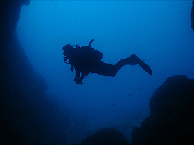 Diver swimming in front of a cave in the twilight hours
