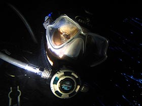 Night diver taking a selfy while diving in Phuket